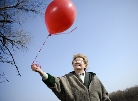 Senior woman outdoors holding red balloon, smiling, low angle view