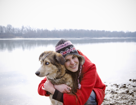 Young woman kneeling by river embracing dog, smiling, portrait