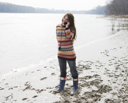 Young woman standing by river, using mobile phone, smiling