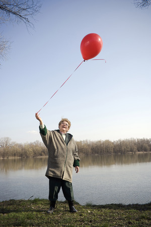 Senior woman standing by river holding red balloon, smiling Stock Photo