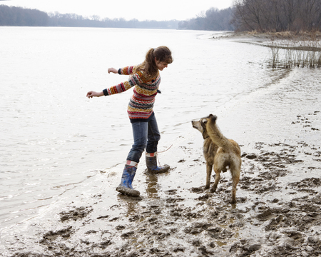 Young woman playing with dog by river