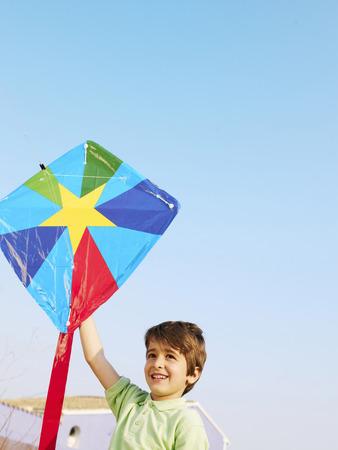 Boy (4-6) outdoors holding up kite, smiling Stock Photo