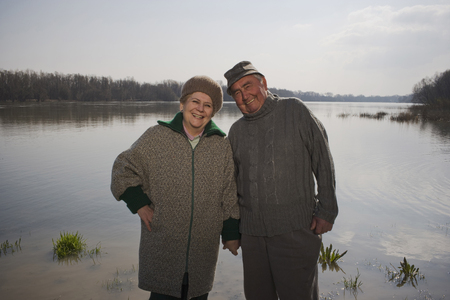 Senior couple standing by river, holding hands, smiling, portrait