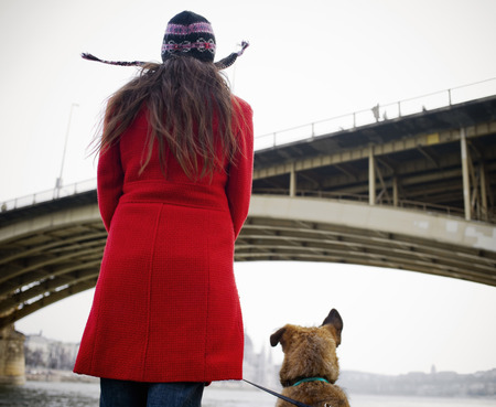 Young woman wearing hat standing by river with dog, rear view