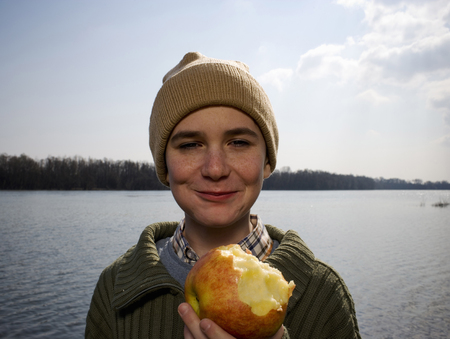 Boy (12-14) standing by river holding out apple, smiling, portrait