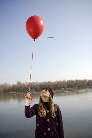 Girl (10-12) standing by river looking up at red balloon on ribbon