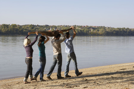 Four friends carrying a log by a lake.
