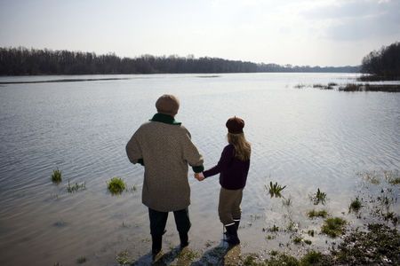 Grandmother and granddaughter (10-12) standing in river, rear view Stock Photo