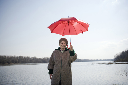Senior woman standing by river holding red umbrella, smiling, portrait