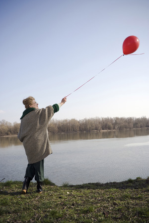 Senior woman standing by river holding red balloon, rear view Stock Photo
