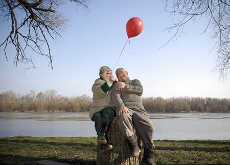 Senior couple sitting by river holding red balloon, smiling