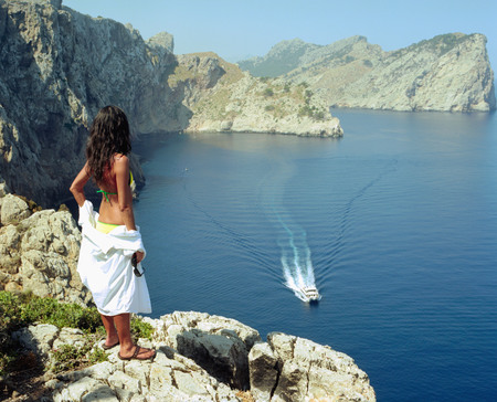 Woman standing on a large rock with a speedboat going by.