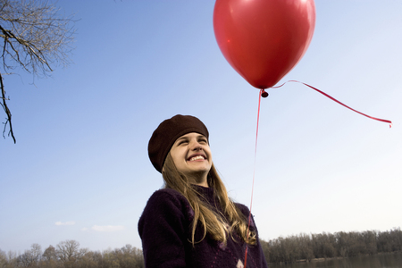 Girl (10-12) outdoors, holding red balloon, smiling