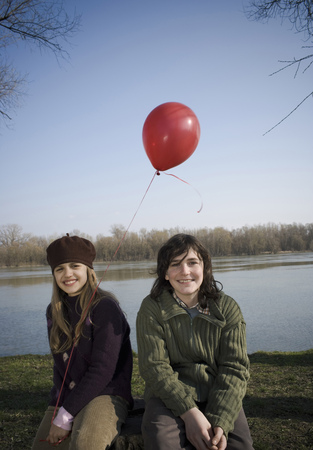 Boy (12-14) and girl (10-12) holding balloon, sitting by river, smiling