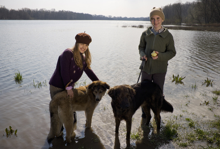 Brother (12-14) and sister (11-13) standing in river with two dogs, smiling Stock Photo