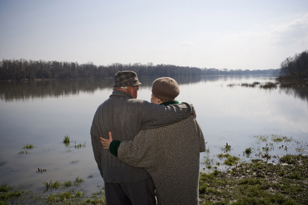 Senior couple standing by river, arms around each other, rear view