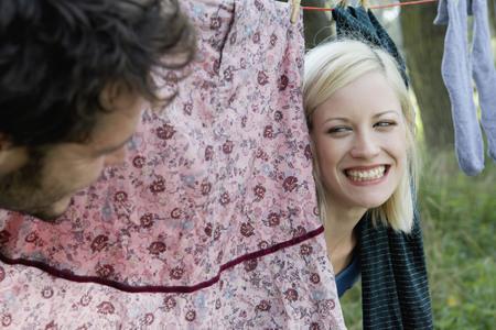 Couple peeking through laundry hanging on clothesline smiling.