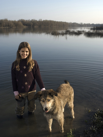 Girl (10-12) standing in river holding dog on lead, smiling, portrait