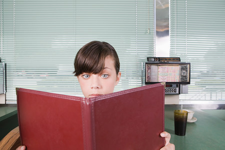 Girl reading a menu in a diner Stock Photo