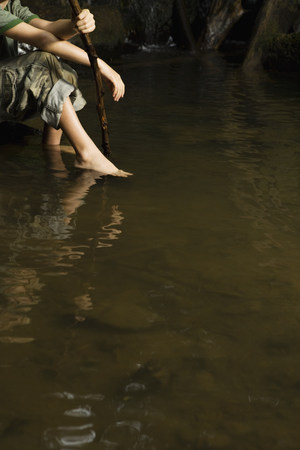 Boy with feet in river Stock Photo