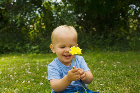 A baby boy holding flowers