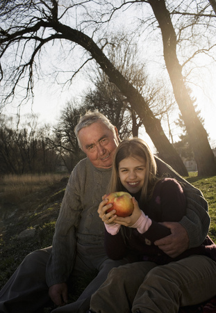 Grandfather and granddaughter (10-12) sitting outdoors, smiling Stock Photo
