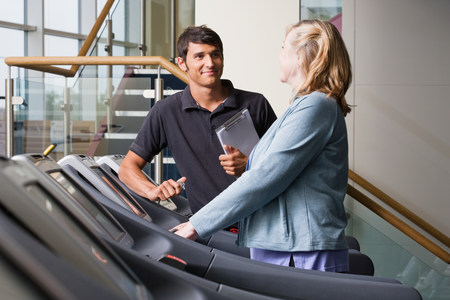 A personal trainer and woman on a treadmill