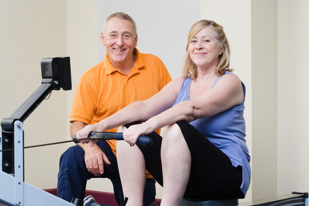 Personal trainer helping a woman on a rowing machine Stock Photo