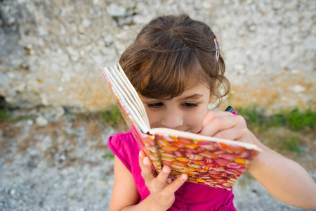 A girl writing in a book Stock Photo - 86035988