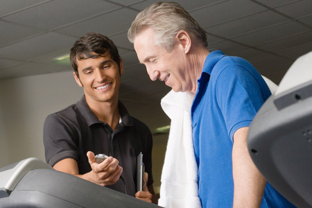 A personal trainer helping a man on a treadmill Stock Photo