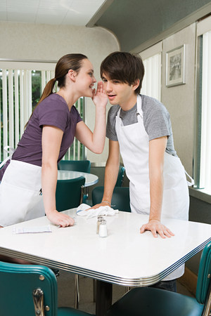 Waitress whispering to colleague
