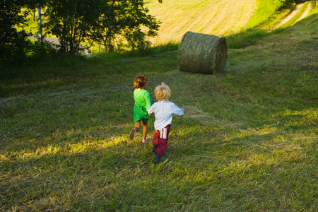 Boy and girl running down a field Stock Photo