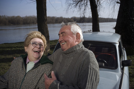 Senior couple standing by car on riverside, laughing