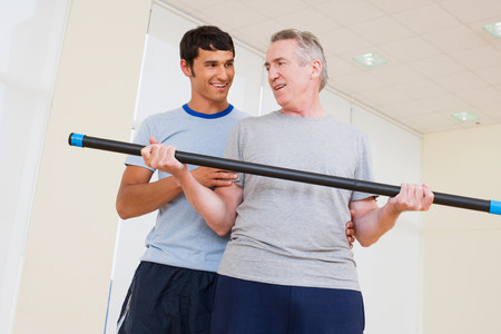 A personal trainer helping a man exercise Stock Photo