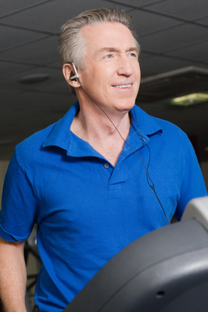 A mature man listening to music whilst exercising