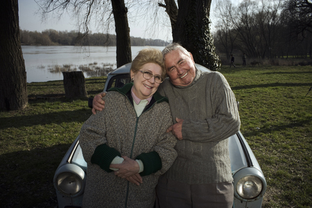 Senior couple leaning on car by riverside, smiling, portrait