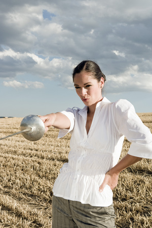 Woman pointing sword in wheat field.