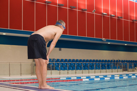 A mature man about to dive into a swimming pool Stock Photo