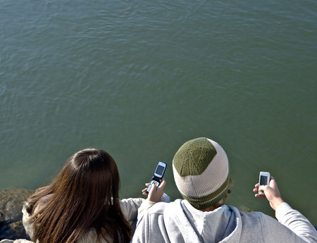 Young couple looking at mobiles