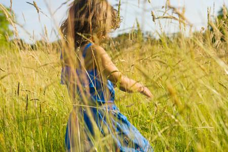 A girl walking through a field of long grass
