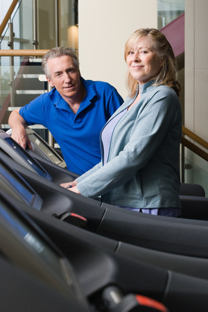 A man and woman using treadmills in the gym