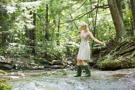Woman walking in river 스톡 콘텐츠