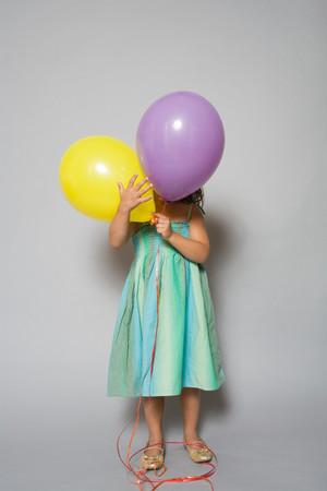 風船の後ろに隠れている女の子
