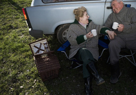 Senior couple having picnic by car, holding cups, smiling