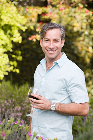 Man outdoors with glass of wine