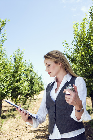Woman with stopwatch in orchard.
