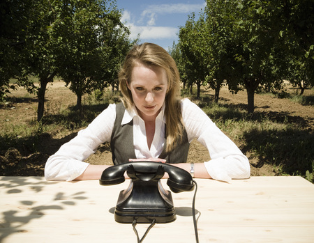 Woman sitting at desk with old telephone in orchard.