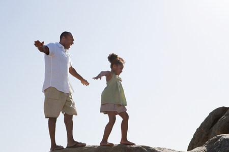 Vader en dochter die op rotsen lopen
