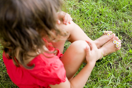 A girl with daisies between her toes