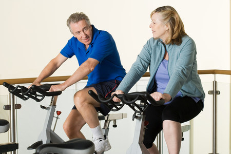 A man and woman using exercise bikes